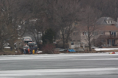 Emergency personnel on the opposite side of the lake in Netcong. To the far right and emergency responder is lying on his stomach attempting to reach the third person from the otherside.