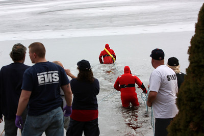 The second emergency responder enters the lake. Both men are tethered to each other by the blue life line which is also tethered to multiple emergency staff on dry land.