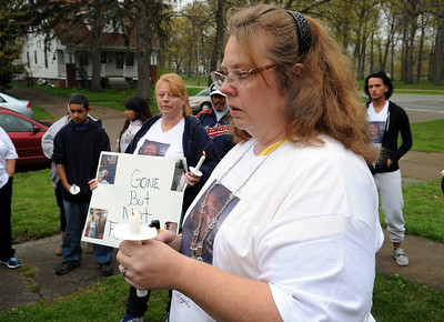 Rebecca Kompton, front, and Rachel Rodriguez, holding sign, at a remembrance and prayer vigil for Lamar 'Mark' Taylor on E. 34th St. in Lorain,  on Apr. 14.  Over 50 people attended the vigil by Interfaith Ministries, in conjunction with family, friends and community leaders.   He was found beaten to death in a yard at 1964 E. 34th St.    Steve Manheim