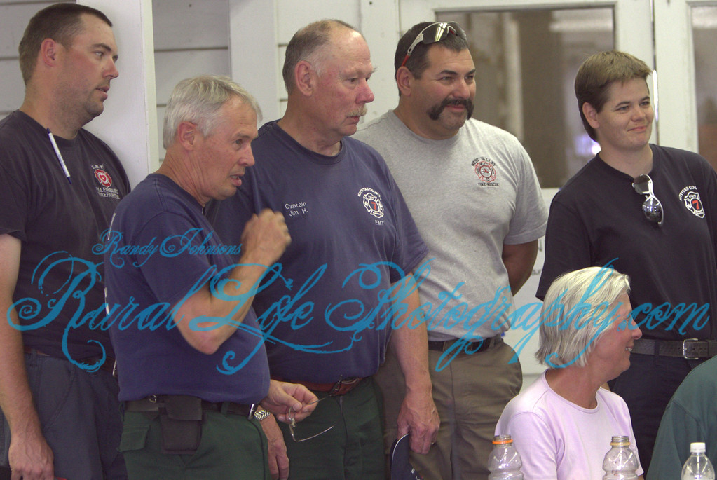 A group shot of fire fighters with some evacuees after these fire fighters were credited by these property owners for saving there house , and dogs kennels, .