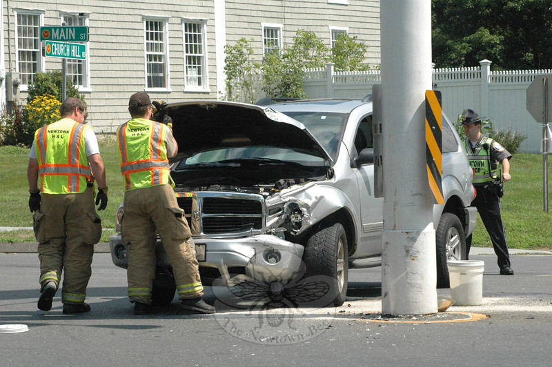Police and Hook & Ladder volunteer firefighters responded to a one-vehicle accident at the Main Street flagpole about 11:25 am on July 24. Police report that motorist Christine Velez, 50, of Trumbull was driving a 2004 Dodge Durango SUV westward on Church Hill Road and then attempted to make a left turn onto southbound Main Street, but while doing so the left front section of the vehicle hit the flagpole. Velez was not injured. Police said they issued her a written warning for failure to drive to the right and for failure to renew a driver's license.   (Gorosko photo)