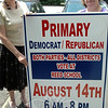 Newtown's Democratic Registrar of Voters LeReine Frampton, right, and Assistant Registrar Carol Mattegat show off new signage that will be posted around the community re-minding qualified residents to vote August 14 in either the Democratic or Republican primaries. Voters from all four local voting districts will cast ballots at a single location, Reed Intermediate School cafetorium, that day between the hours of 6 am and 8 pm.   (Voket photo)