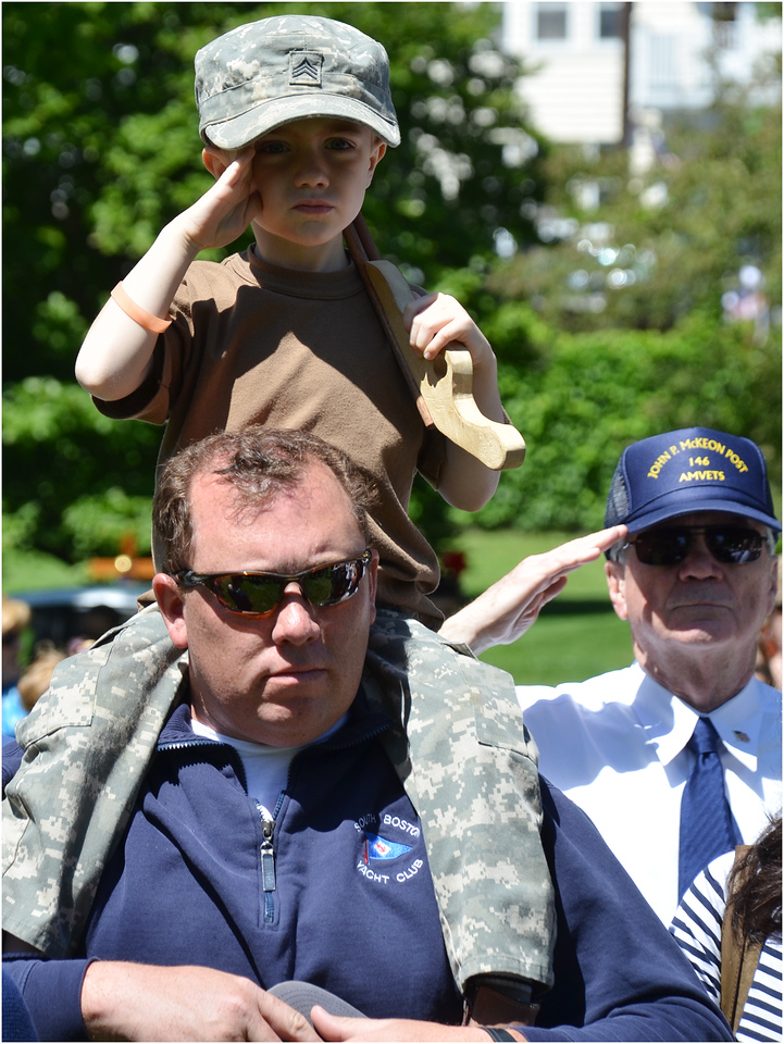 Conrad Magoon, age 4 of Dorchester, joins in salute while on the shoulders of his uncle, Ryan Toland of South Boston.