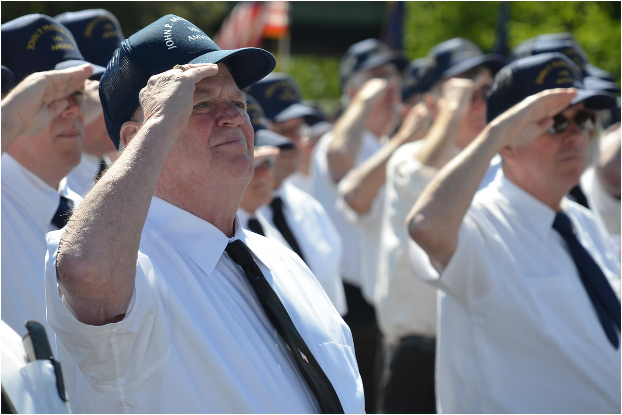 Edward Reardon, a McKeon Post member originally from Neponset, joins comrades in salute before the start of the parade to Cedar Grove Cemetery.