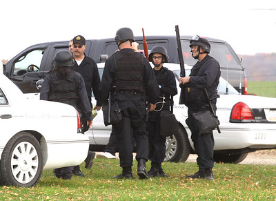 27oct09 PRISON EXERCISE Officers wearing tactical gear talk as another group of officers negotiates with at least one person who was barricaded inside a home on prison property.