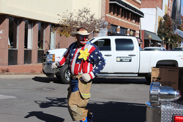 A clown from the Muskogee Fire Department darts around a fire truck to hand out candy to young people during the parade.