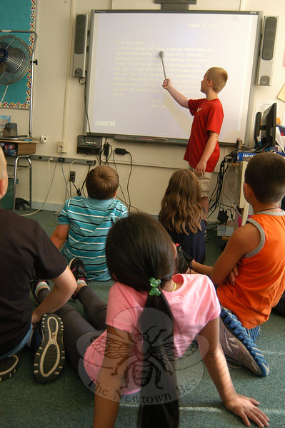Sandy Hook School third grade student Aidan Berry helps his class read aloud a morning message on Friday, August 31. (Hallabeck photo)