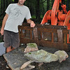 Sculptor Ethan Currier of Bainbridge Island, Wash., stands next to stones he selected at Sticks and Stones Farm that will become the rooster centerpiece for the September 15-16 Newtown Arts Festival at Fairfield Hills. Mr Currier grew up on the moss and stone farm on Huntingtown Road and is spending a three-week vacation sculpting and exhibiting at the festival. (Crevier photo)