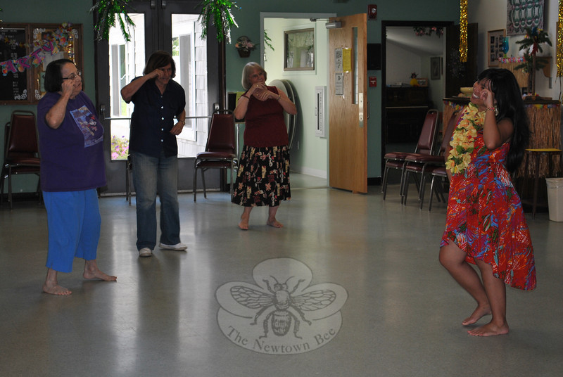 Newtown Senior Center members, from left, Ann Marie Macey, Joyce Goldin, and Janice Gartner follow the lead of Polynesian dance instructor Jasmin during the center's weekly hula dancing class on August 30. The class is held at the Senior Center each Thursday, at 3 pm, and both men and women are invited to attend, for a cost of just $1 per class. (Crevier photo)