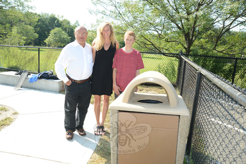Resident Howard Lasher, left, and Parks and Recreation Director Amy Mangold stand with Adam Mangiafico at Newtown Skate Park. Mr Lasher recently purchased the permanent recycling container in front of the group to support Adam's efforts to help clean up the skate park. (Bobowick photo)