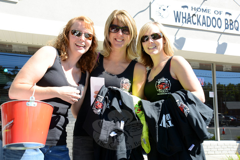Karin and Krista Halstead stand to the left and right of friend Sue Miller as the three all promote raffle ticket sales for the third annual Firehouse Ride to benefit Newtown Hook & Ladder Company #1. (Bobowick photo)