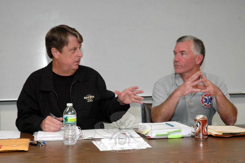 Kevin Cragin, chairman of the Board of Fire Commissioners, left, and Michael Burton, the Sandy Hook Volunteer Fire & Rescue Company representative on the board, discuss an issue at a September 24 session of the seven-member panel. (Gorosko photo)