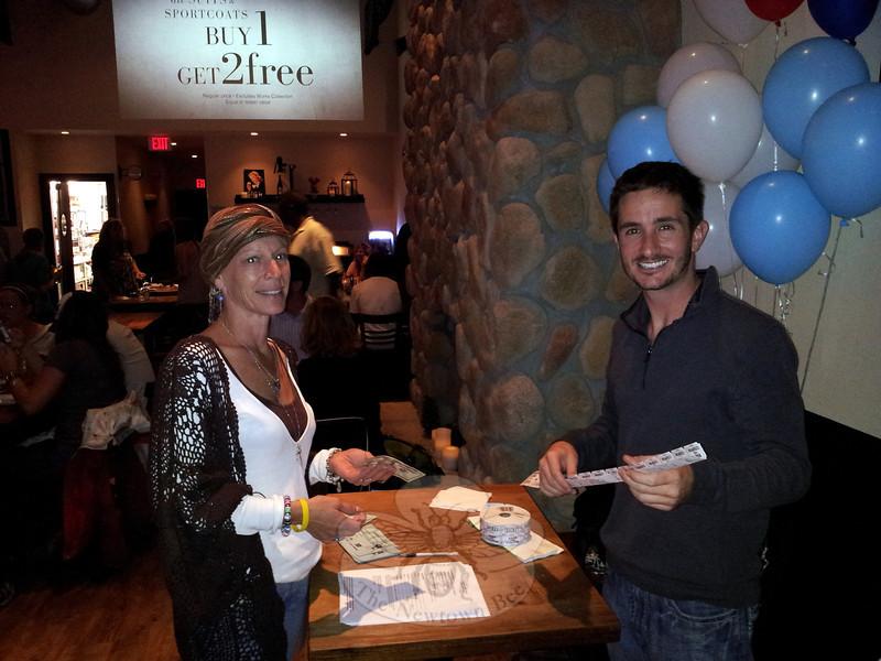 Newtowner Marc Landolfi dispenses a strip of raffle tickets to cancer survivor Beth Michalka of Monroe, who happened to be dining at Pub 25 in Plaza South during his fundraiser for Team Determination, an American Cancer Society initiative that will bring Mr Landolfi to the New York Marathon in November raising support for cancer research. (Voket photo)