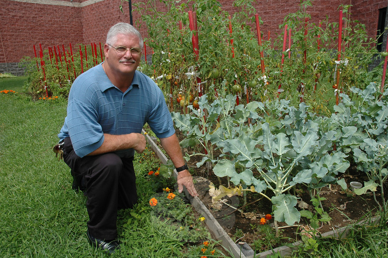 Garner Correctional Institution Recreation Supervisor Carl Ruegg displays a vegetable bed in a prison courtyard where inmates grow organic vegetables. (Gorosko photo)