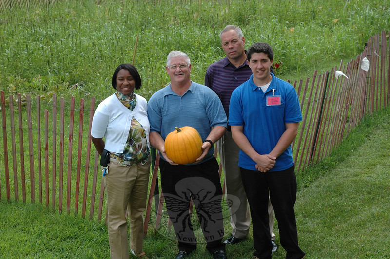 Garner Correctional Institution Recreation Supervisor Carl Ruegg holds one of the many pumpkins grown at Garner's organic garden near the high-security prison's helipad. Also pictured, from left, Amonda Hannah, who is Garner's deputy warden for programs and treatment, Garner Warden Scott Semple, and Adam Meehan, who is a recreation intern at Garner. (Gorosko photo)