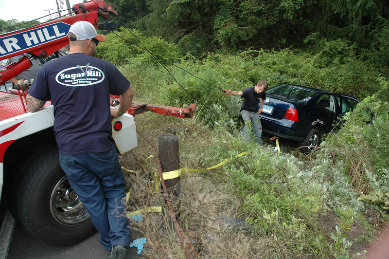 A wrecker crew works to pull a Volkswagen Jetta sedan up an embankment after the vehicle went off the road near 143 South Main Street at about 3:30 pm on August 1. Police said that a man who was driving the sedan northward on South Main Street drove off the right road shoulder, with the vehicle then rolling down the bank. Police said the unidentified man was transported to the hospital by ambulance for treatment of non-life-threatening injuries. Volunteer firefighters responded to the accident. The incident caused travel delays in the area. Details on the accident were not available from police before the deadline for this edition of The Newtown Bee.      (Gorosko photo)