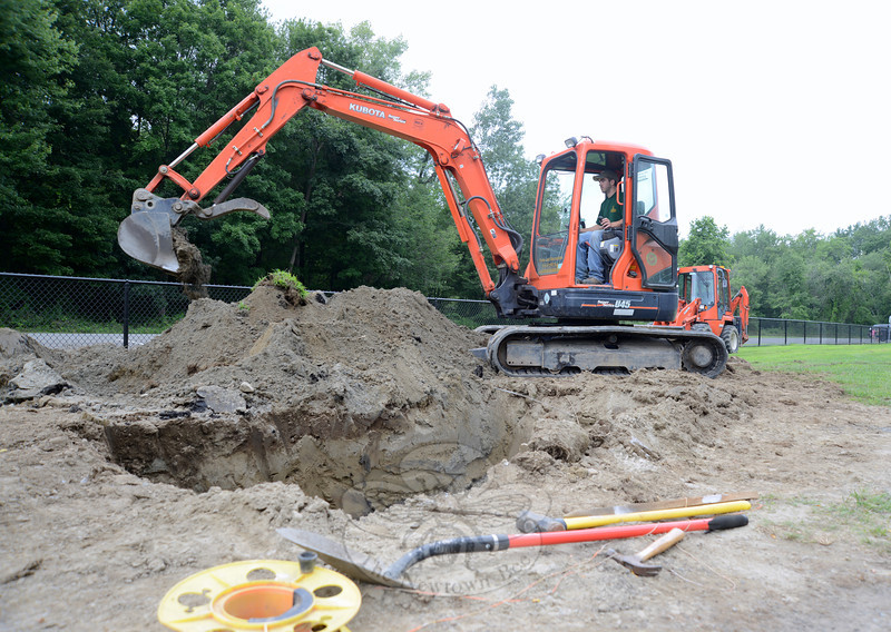 Dan Murtha uses an excavator to dig out holes for concrete footings Wednesday. He and Robert Fritzinger were at Dickinson Park this week working on the band shell project.   (Bobowick photo)