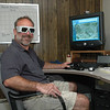 Richard A. Markey, vice president/office manager at Golden Aerial Surveys, Inc, in Hawleyville, is sporting a set of specialized eyeglasses that allow the wearer to view highly realistic three-dimensional aerial photography on a computer monitor. A view of Brookfield Center is displayed on the screen.   (Gorosko photo)