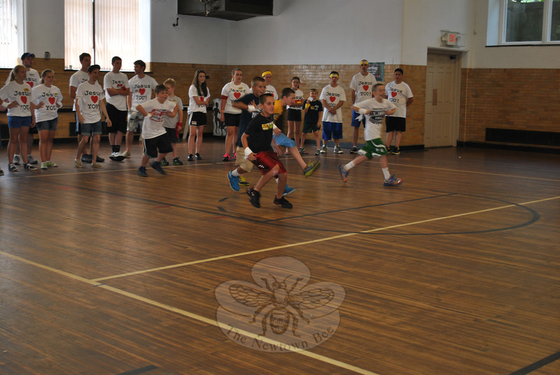 "Pretending to be zoo animals, children race forward in a game of ""Feed The Animals,"" Tuesday, July 24, one of several team-building games played during the week of July 23 by boys and girls in grades kindergarten through sixth attending the Faith at Newtown Vacation Bible School program in the Edmond Town Hall gymnasium. Pastor Timothy Kuhn said that 20 youth from the Ruskin, Fla., First Baptist Church assisted at the camp, held each day from 1 to 3 pm, staying at the homes of congregation members. Using the theme of ""Big Apple Adventure,"" participants formed teams with names connected to New York City — such as the Yellow Taxis — and competed in a variety of games each day to accumulate the most points. Points were earned not only through winning games, but by team behavior, knowledge of Bible verses, and success in team-building exercises. 	   (Crevier photo)"