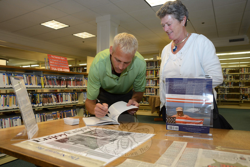 The Patriotic Spirit author and photographer Chris Seman signs a copy of his book for Barbara Johann, who attended his book signing and presentation Friday, July 22, at the C.H. Booth Library.   (Bobowick photo)
