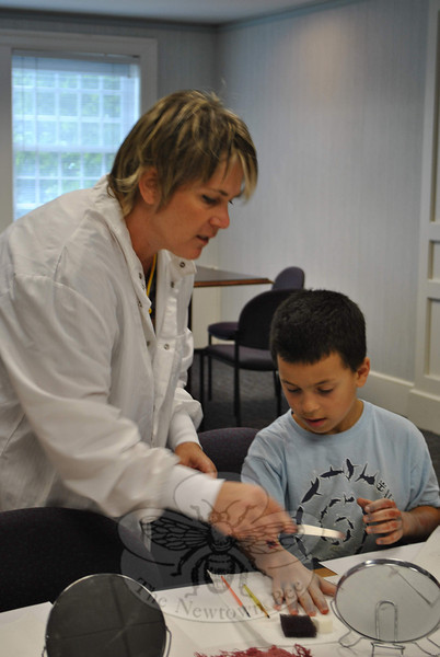 Theatrical makeup expert Caroline Wilcox shows 10-year-old Owen Baillargeon how to create a realistic burn during the Zombie Response Team workshop, Monday, July 30, at the C.H. Booth Library.   (Crevier photo)