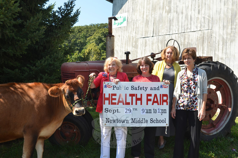"From left, organizers Mae Schmidle, Donna Culbert, Judy Blanchard, and Della Schmid ""audition"" one of the Castle Hill Farm cows for a possible starring role at the 19th annual Newtown Health and Public Safety Fair, which will be held at the Newtown Middle School on Saturday, September 29, from 9 am to 1 pm.   (Voket photo)"
