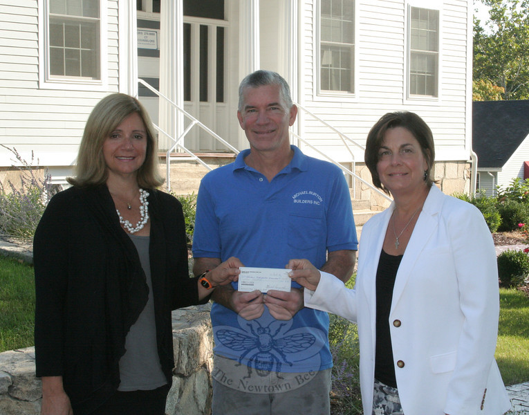 Michael Burton, the president of Sandy Hook Organization for Prosperity (SHOP), met with Stephanie Gaston, left, and Julie Savino on Friday, September 14, to present a check on behalf of SHOP to the women. Mrs Savino is the president of Newtown Scholarship Association, and Mrs Gaston is NSA's awards chairperson. The donation from SHOP will be used, said Mr Burton, to establish a new scholarship to be awarded annually to a student from Sandy Hook planning to study business. The award will be presented for the first time next spring.   (Hicks photo)