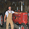 Jay Chaikin, owner of Reclaimed Relics and host of the new National Geographic Channel  series Abandoned, stands next to a 1945 tractor in one of the 1800s barns on the Amaral property on South Main Street, across from Amaral Motors. The tractor is one of many treasures Mr Chaikin hauled out of the barns the week of August 13. (Crevier photo)
