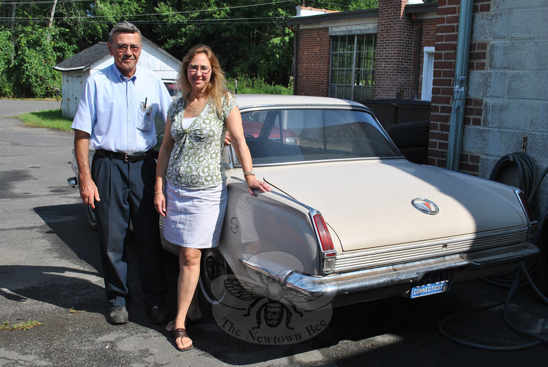 Daniel Amaral and daughter Cathy Amaral Freitas stand next to a 1964 Plymouth Valiant, the one item they did not include in the sale this summer of the contents of the barns on South Main Street, across from Amaral Motors. That a television show would prove the answer to their prayers as to how to get rid of the barns' contents was not a solution they even imagined. (Crevier Photo)