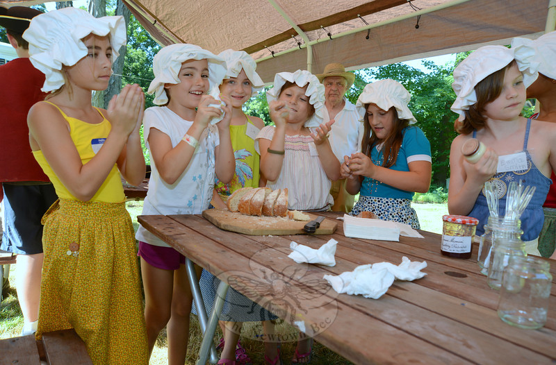 The children attending history camp at the Matthew Curtiss House on Main Street this week got a lesson in butter making. Shaking small jars to make butter to enjoy with an afternoon treat of bread with jam are, from left, Molly Moran, Melina Cummings, Julia Bren-nan, Emma Wologodczew, Kaylee Timmons, Emma Smith, and hidden from view, Tania Se-queira. (Bobowick photo)