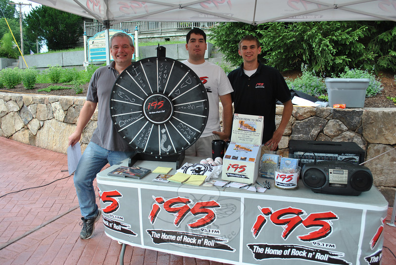 "On the corner where Washington Avenue and Riverside and Church Hill Roads come together, radio station i95 ""The Home of Rock and Roll"" in Brookfield, set up a tent during SHOP's Peace, Love & Sandy Hook event, giving away promotional materials for just the spin of a wheel. From left, afternoon DJ and program director Tim Sheehan, intern Gabe Rosen, and Don Gehring, promotions assistant, were ready to greet visitors.  (Crevier photo)"