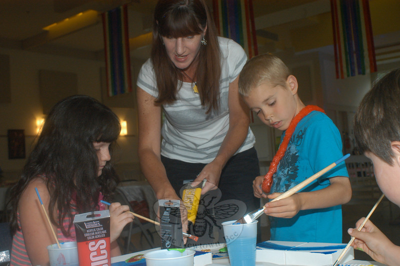 Karen Zatulskis helps her daughter, Grace, while Jeremy Pankow paints his heart for Hearts of Hope during the HealingNewtown opening reception. (Hutchison photo)