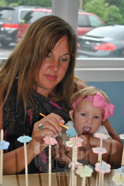 Jennie Nowacki juggles 6-month-old Madeline as she glazes Kindness Coins.  (Crevier photo)