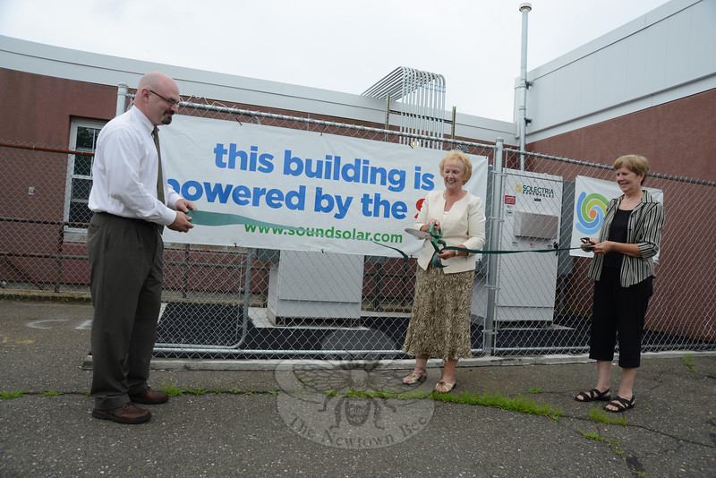 First Selectman Pat Llodra raises the ceremonial scissors and slices through a ribbon celebrating the solar install at Newtown Middle School. With her, left, is State Economic Development Director Robert Michalik, Jr, and Sustainable Energy Commission Chairman Kathleen Quinn.   (Bobowick photo)