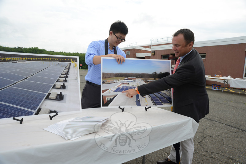 Altus Power Management Managing Partner Tom Athan, with the company that supplied funds for the project, points to pieces he set in place. Setting the poster in its base is Henry Cheung with sustainable energy supplier Sound Solar Systems LLC.   (Bobowick photo)