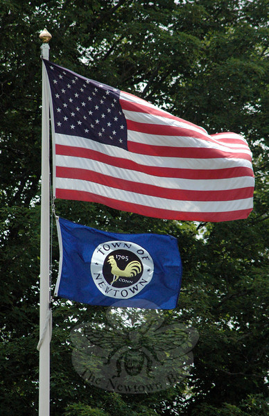 The town is now flying its new municipal flag below the US flag on a pole near the southern entrance to Newtown Municipal Center at 3 Primrose Street. Town Clerk Debbie Aurelia and Human Resources Administrator Carole Ross derived the flag's design from the town seal. The new flag is on the cover of the recently published annual town report for 2012. (Gorosko photo)