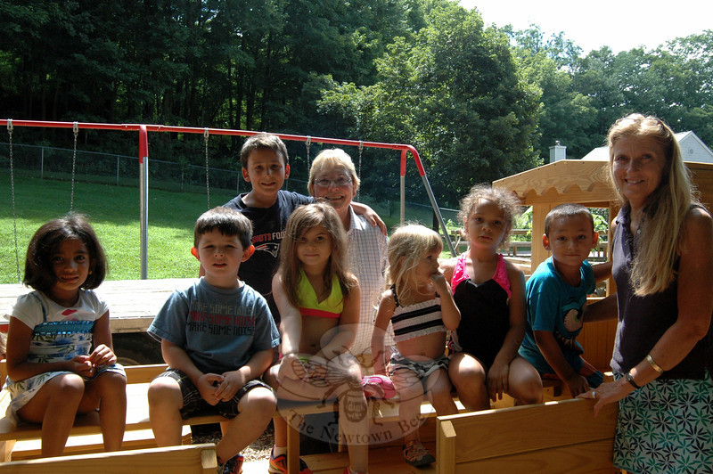 Children's Adventure Center students sat on a newly installed wooden train on the preschool's playground. Children's Adventure Center Director Judy Sims, back center, and instructor Lisa Bruno stood with the students and Ms Sims's grandson, Justin Sims, back left. (Hallabeck photo)