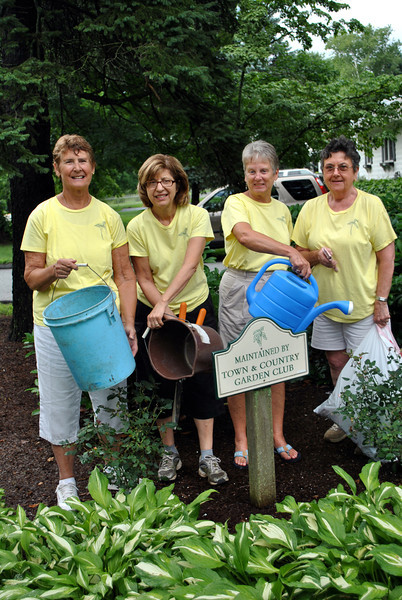 "Members of the Town & Country Garden Club of Newtown, from left, Co-presidents Diana Johnson and Josie Schmidt, Emi Lydem, and Barbara O'Connor display the buckets and pails used to hand water annuals in the island gardens maintained by the club. The local garden club supports three of the floral islands that beautify intersections in the Borough: one at the intersection of Queen Street and Church Hill Road; one at the intersection of Glover Avenue and Route 25; and one where Queen Street and Glover Avenue meet. An ongoing difficulty has become a crisis in the recent spells of hot weather, that of adequately watering the island gardens. Established shrubs and native plants can withstand a dry spell, but rose bushes, potted plants, and annuals suffer. Members of a group that is ""maturing,"" according to Ms Johnson, are lugging buckets of water to care for the plants. It is a chore that is not only physically difficult, but does not provide sufficient water for the plants in need. Town & Country is hoping that stronger individuals or members of scout groups or other clubs might be able to take on the task of keeping the gardens watered this summer and into the fall. To volunteer, contact Town & Country Garden Club member Sandy Motyka at 203-426-0378. (Crevier photo)"