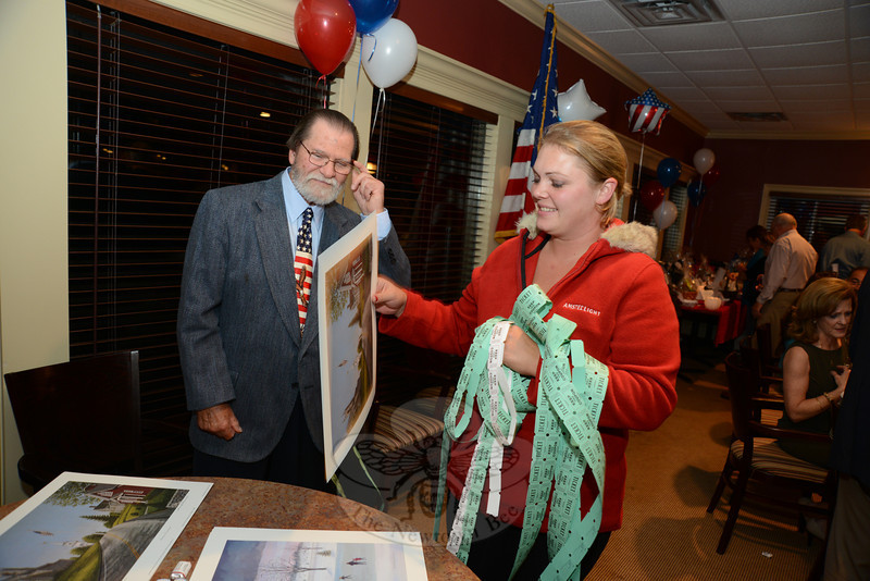 VFW Ladies Auxiliary member Cynthia Todd holds an armful of raffle tickets while she talks with local artist David Merrill about the Newtown scenes on the table. His prints were part of the fundraiser for a veterans mural Mr Merrill is completing for Project Newtown Troops and Veterans.   (Bobowick photo)