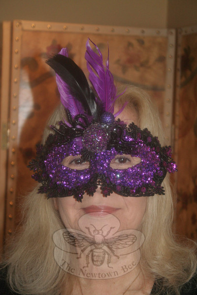 "Rosemary Rau models one of the masks that have been decorated and donated for this year's Newtown United, LLC fundraiser. ""Newtown United ArtFULL — All About Halloween"" will be held on Saturday, October 27, less than a week before Halloween, and attendees are being encouraged to go all out with costumes.   (Hicks photo)"