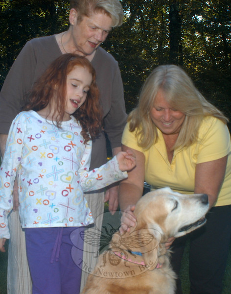 "Gracie, a Sandy Hook golden retriever run over by a Federal Express driver back on August 1, was the center of attention at her recovery/belated birthday party on Sunday, September 30. Pictured with Gracie are, from left: family friend Amy Steinbroner, 7, Sherry Paisley, owner of the pooch, and Newtown Animal Control Officer Carolee Mason, who found Gracie — injured and scared several hours after the incident. Ms Paisley had more than 50 friends and family over at her Walnut Tree Hill residence for cake (and dog treats), and to make donations to the Newtown pound. More than $500 was donated by guests who also came with dog toys and treats. Gracie, despite having some scars and having been through some $4,500 in veterinary work, was full of life and energy as she greeted guests with a wagging tail. FedEx made good on coming though with paying for the vet bills, but Ms Paisley — frustrated with what she called an insulting FedEx letter suggesting that the accident was her fault because the dog was unsupervised in her driveway — is seeking more. She has asked FedEx to make a donation to the pound. ""I want them to be so sick of me that they pay me money to go away,"" she said.   (Hutchison photo)"