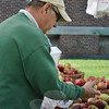"Robert Dachenhausen chooses apples at the Southbury Daffodil Hill Growers' booth. The organic and locally grown fruits and vegetables draw Mr Dachenhausen to the market each week. ""The taste is so much better and finer,"" says Mr Dachenhausen.    (Crevier photo)"