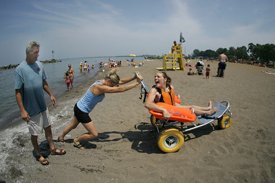 29JUN12   Samantha Taylor with a gleeful scream of delight-- checks out the special beach equipment --the Mobi Chair--a type of amphibious beach wheelchair--that's available at Lakeview Park. Mom  Renee pushes the chair and dad Aaron is far left.        Photo  by Chuck Humel