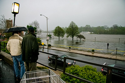Curious bystanders watch as the Merrimack River overflows its banks on River St. in Haverhill, MA.