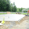 Wet concrete sets at Dickinson Park while the frame for a band shell sits in the distance. Soon, performers will have shelter as they entertain. (Bobowick photo)