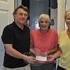Ed Raymond, left, treasurer for Sandy Hook Organization for Prosperity (SHOP) and PJ's Laundromat owner and SHOP member Sharon Doherty, right, present a very appreciative Faith Food Pantry Director Lee Paulson with a check for $500, Tuesday, August 14. SHOP raised funds for local charities at a wine tasting/silent auction held in June at Stone River Grille on Glen Road, where owner Gary Seri provided space and appetizers for nearly 100 attendees. Newtown Scholarship Association and Newtown Youth & Family Services will also be recipients of SHOP's generosity, said Mr Raymond. (Crevier photo)