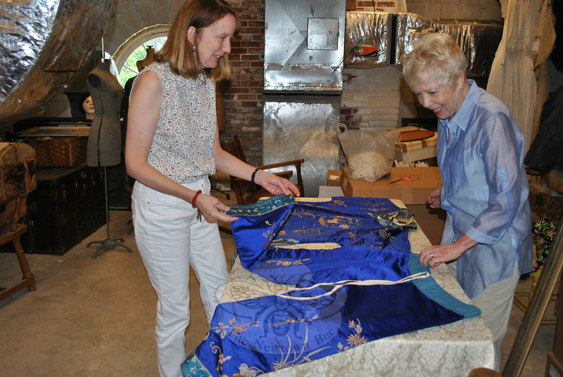 """Reference librarian Andrea Zimmermann, left, and library curator Mary Thomas look over a two-piece ceremonial """"pien-fu"""" donated by Ms Thomas, from the estate of William Upshaw in Hawleyville. The pien-fu will be properly stored and become part of the library's historic textile collection. (Crevier photo)"""