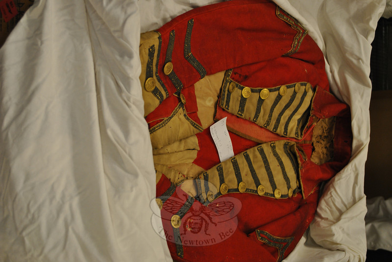 A red wool uniform of a yet unidentified military branch and era is among the treasures un-covered in the library attic, as volunteers catalog the hundreds of textile items there. (Crevier photo)
