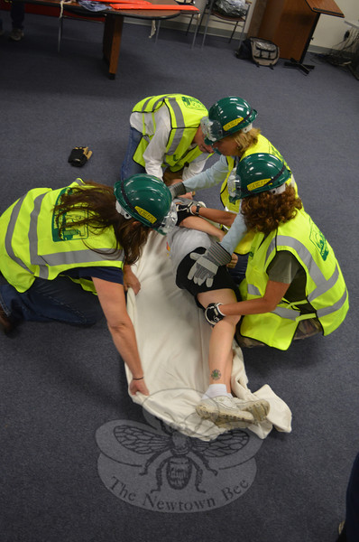 "Newtown CERT volunteers, clockwise from left, Debbie Aurelia, Paul Ludanyi, and Toni Baranowski join Ridgefield volunteer Gerri Lewis learning how to load and carry Karin Halstead, who is leading part of the training, playing an injured ""victim.""(Voket photo)"