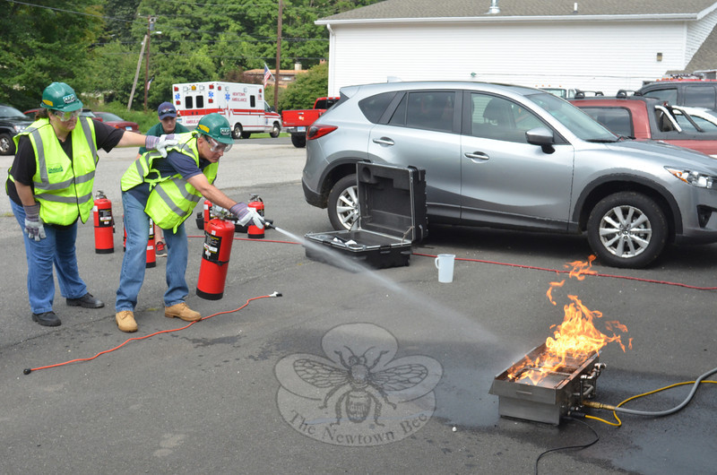 Newtown CERT volunteers Jean Ellicott and Jeff Jorgenson run through one of the fire extinguisher exercises during the graduation certification August 11 at the Sandy Hook Fire & Rescue headquarters. (Voket photo)